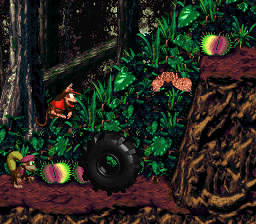 The Kongs jumping toward a tire, which are needed to reach higher areas in Jungle Jinx