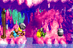 Dixie Kong holding a Steel Barrel at the Koin at the end of Bazza's Blockade in the Game Boy Advance remake of Donkey Kong Country 3