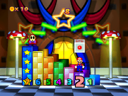 Game Guy's Lucky 7: Mario standing on the second pillar; and above him is a rolling die waiting to be hit. From Mario Party 3.