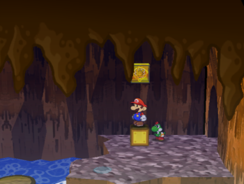Mario next to the Shine Sprite in the floating barrel room of Pirate's Grotto in Paper Mario: The Thousand-Year Door.