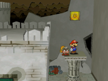 Mario next to the Shine Sprite on the roof of the rightmost column in the center room of level 1 of Rogueport Sewer in Paper Mario: The Thousand-Year Door.
