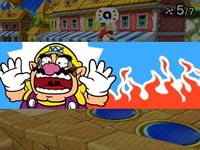 Wario being hit by a Lava Bubble from Coinathlon in Mario Party: Star Rush