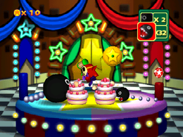 Game Guy's Sweet Surprise: Two differently sized Chain Chomps devouring their own cakes. From Mario Party 3.