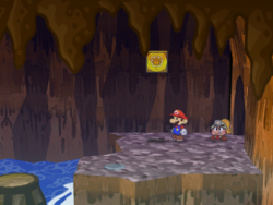 Screenshot of Mario at a hidden? Block location in Pirate's Grotto, in Paper Mario: The Thousand-Year Door.