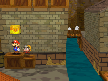 Mario next to the Shine Sprite in the back-east corner of the east Rogueport room in Paper Mario: The Thousand-Year Door.