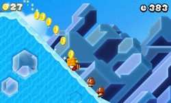 Mario. wearing a Gold Block, sliding down an icy hill towards some Goombas in World 4-3.