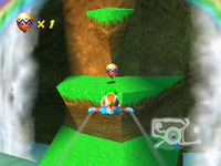Tiptup flies to the Golden Balloon on a grassy ledge to the left of Wizpig's stone head in Diddy Kong Racing.