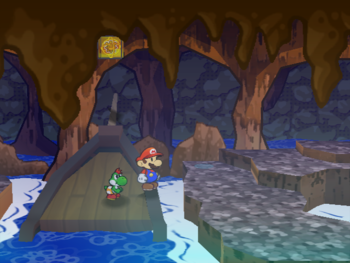 Mario next to the Shine Sprite near the entrance of the Pirate's Grotto in Paper Mario: The Thousand-Year Door.