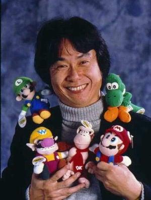 A photo of Shigeru Miyamoto along with his toy characters