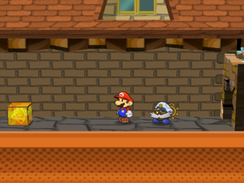 Mario next to the Shine Sprite after the wall to the left of the store in west Rogueport in Paper Mario: The Thousand-Year Door.