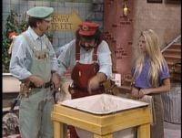 Mario and Luigi begin to show their expert plumbing skills to Nicole Eggert.